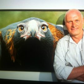 Artist Tony Pridham standing in front of a large painting of a Wedge-tailed eagle