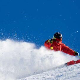 Skier on snow with blue sky